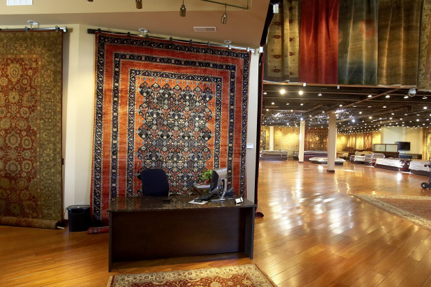 Interior of the Cyrus Artisan Rugs showroom with area rugs on display
