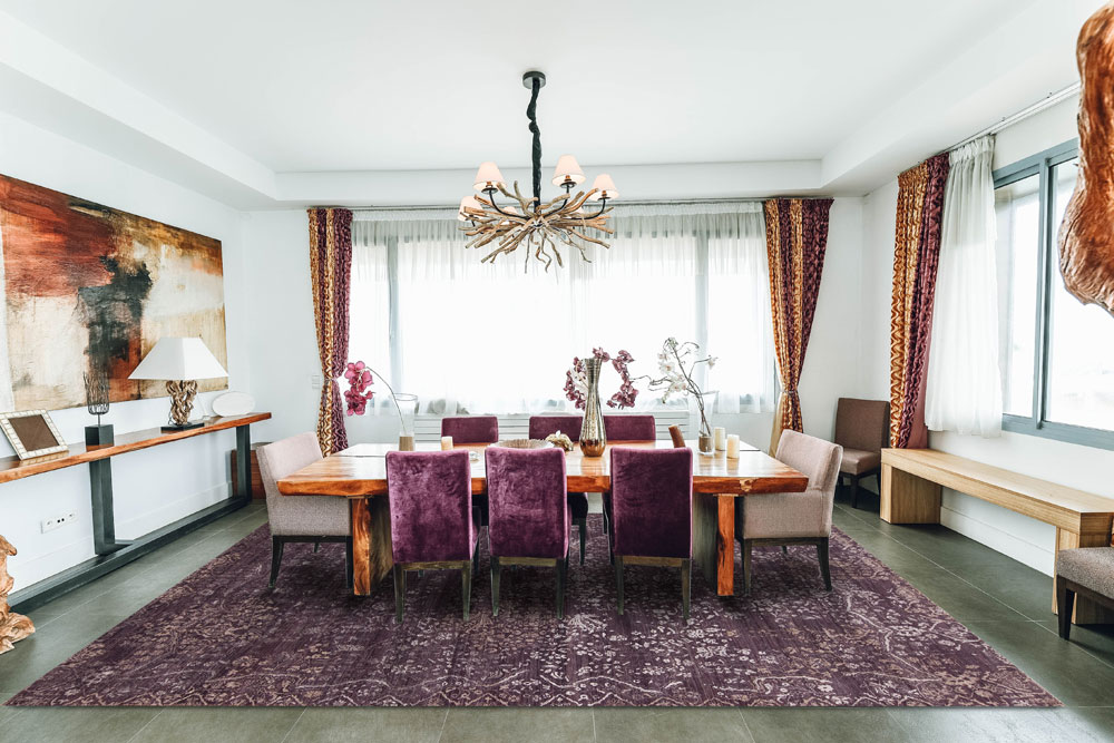 a purple area rug adorns a dining area floor