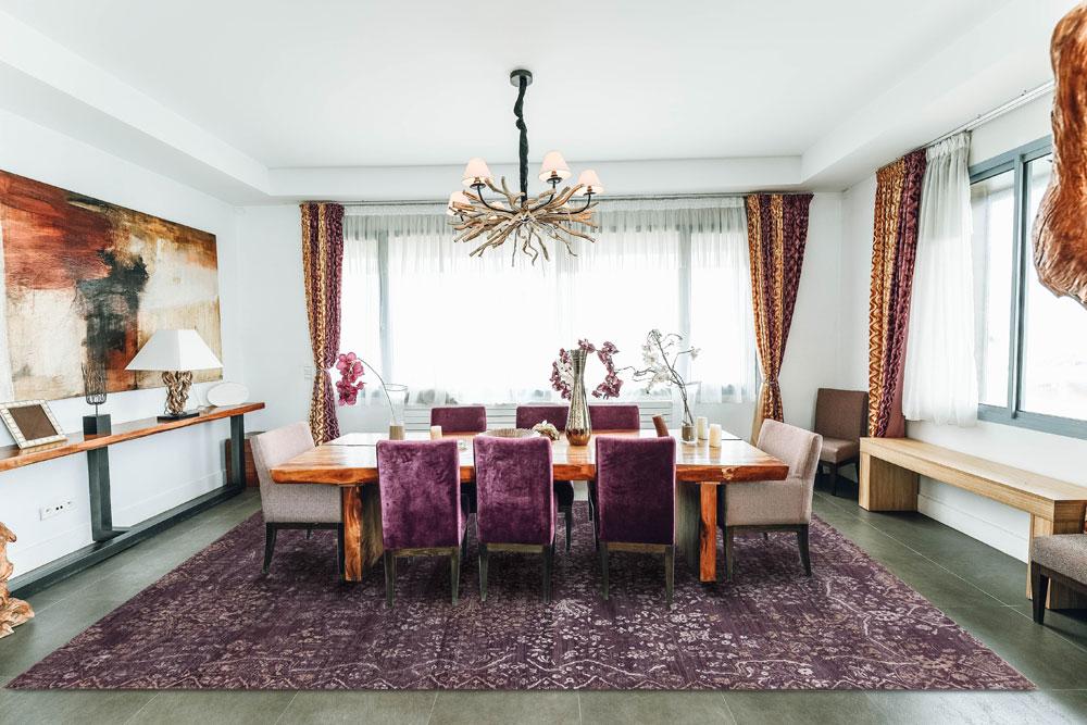 a purple area rug adorns a dining area floor