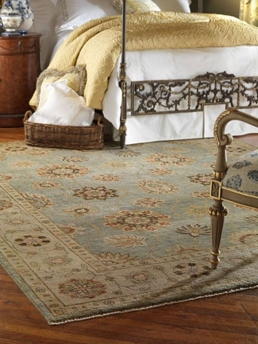 vintage rug placed on top of a wooden floor in a bedroom