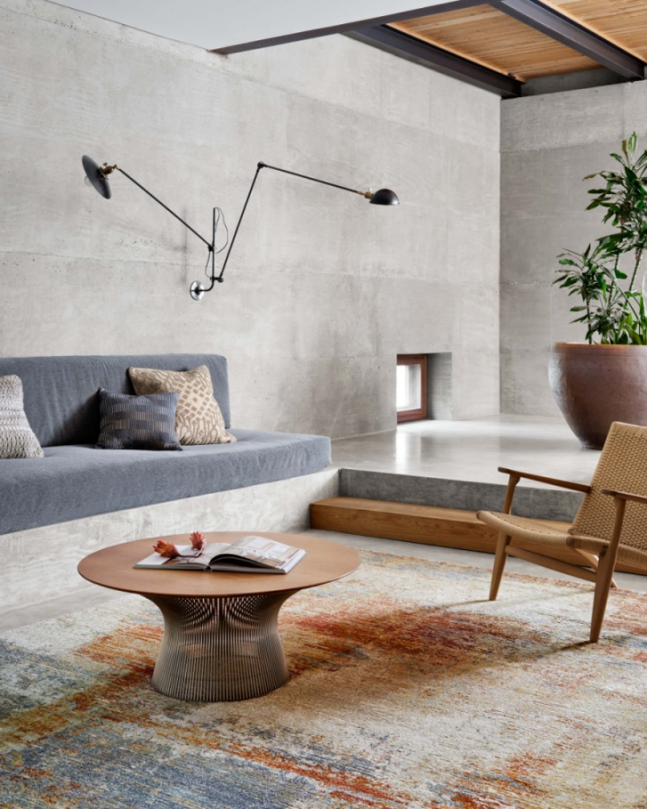 oversized rug softens mid-century living room with raw concrete