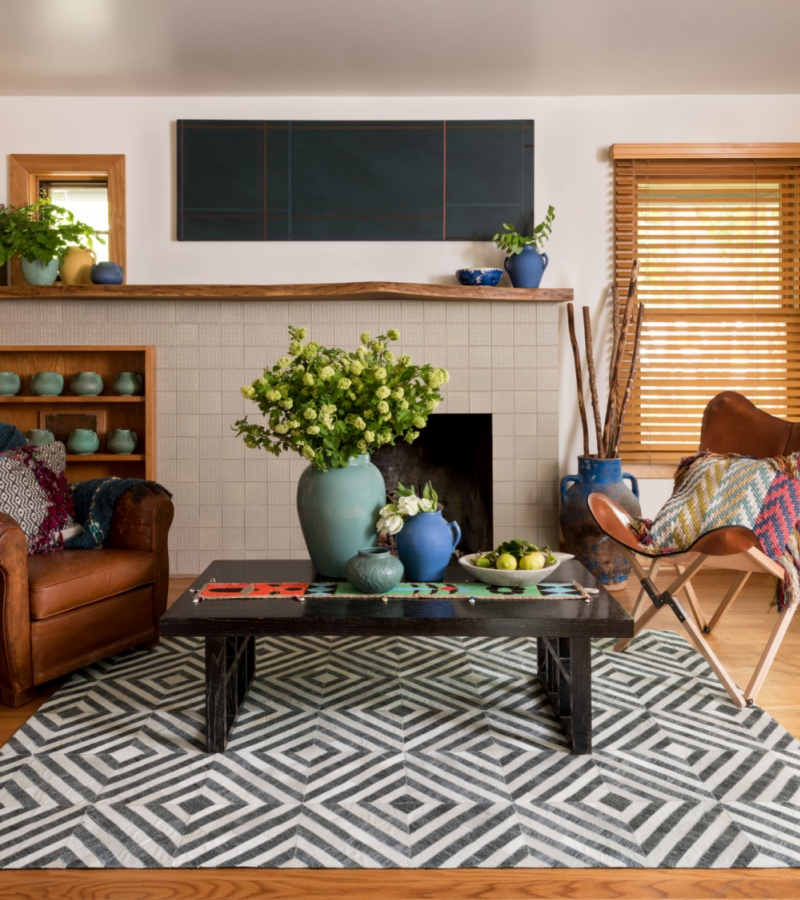 leather chairs, ceramics, and wooden elements atop a rug